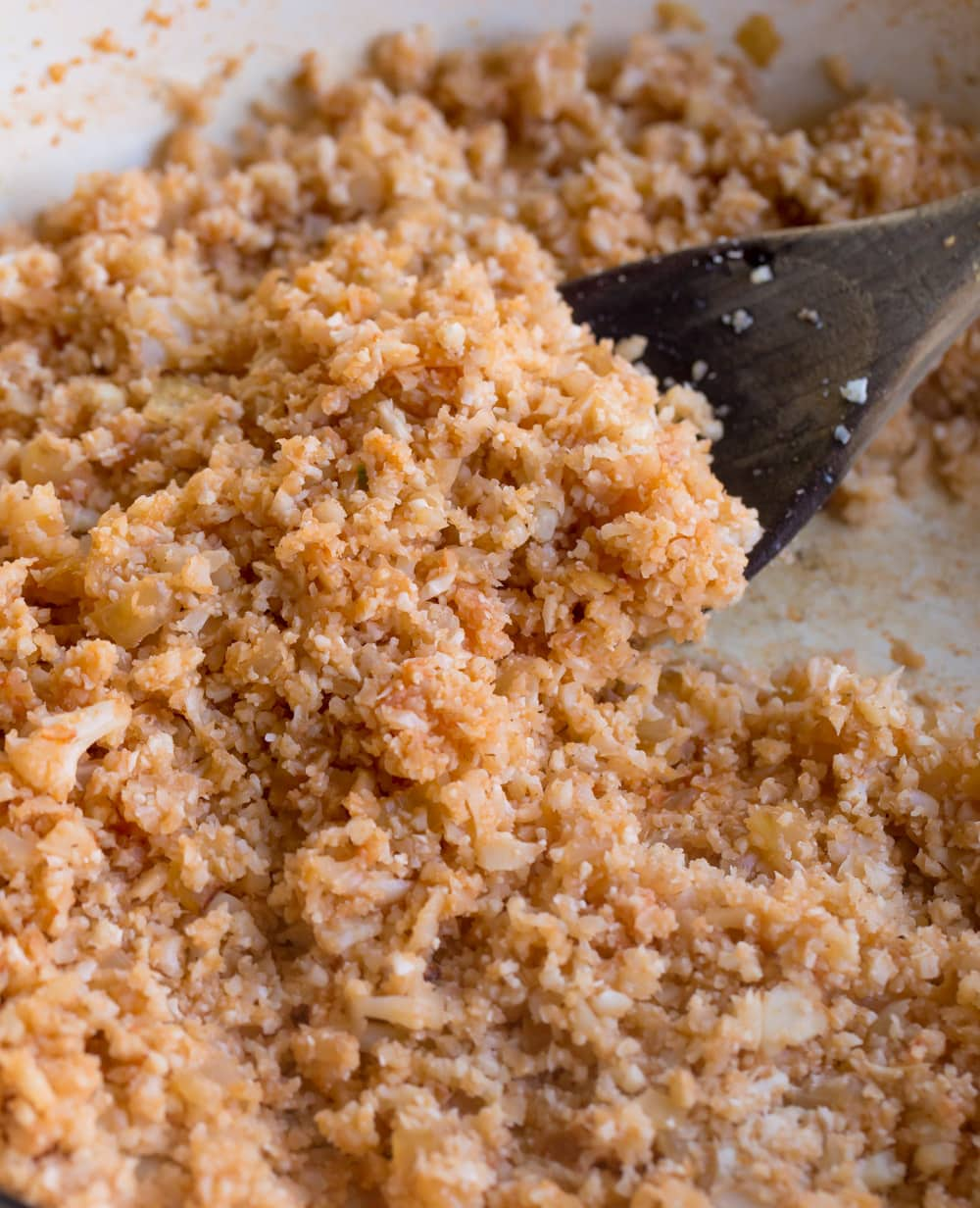 Pan with red riced cauliflower and wooden spoon.