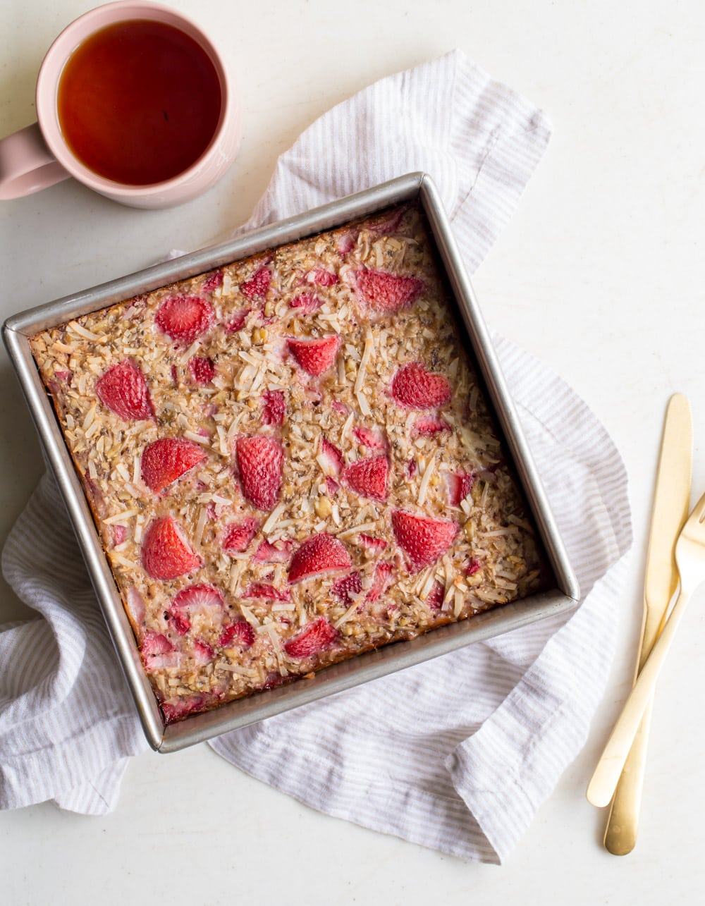 Baked strawberry and coconut mixture with nuts and chia seeds. A cup of tea in the background.