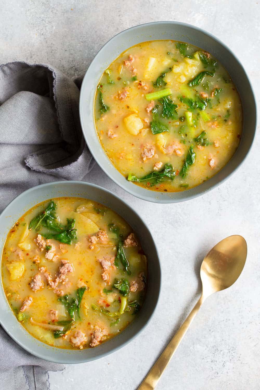 Two bowls of zuppa Toscana with a gold spoon on a gray background