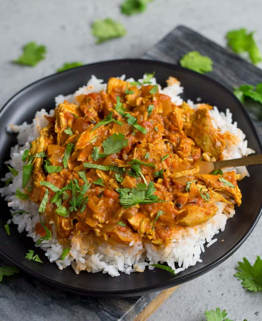 Chicken Tikka Masala over a bed of white rice and cilantro on top.