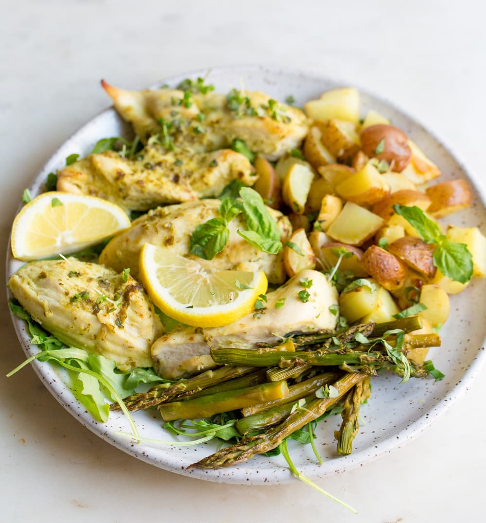 chicken, asparagus, and potatoes on a white plate with lemon slices.
