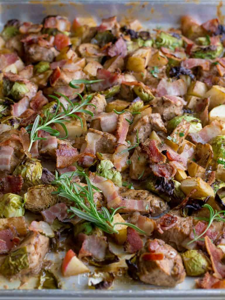 Sheet pan with chicken, bacon, Brussels sprouts, apples, and rosemary on top.