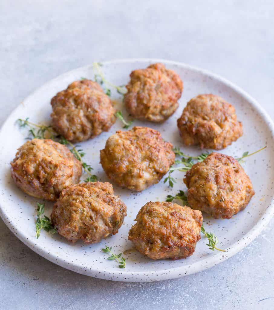 Sausage patties on a plate with fresh thyme sprigs