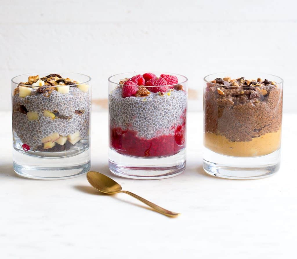 Three glasses of chia pudding, all different flavors with a gold spoon