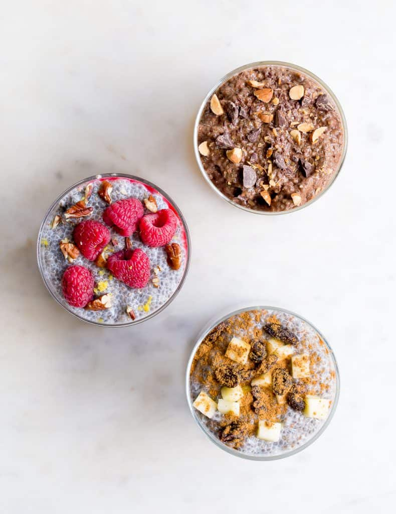 Overhead view of three different chia puddings on a white background.