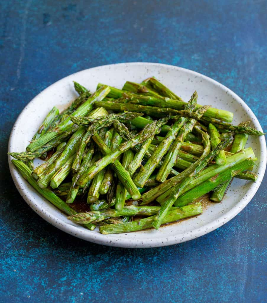 blue background with a white plate of roasted asparagus