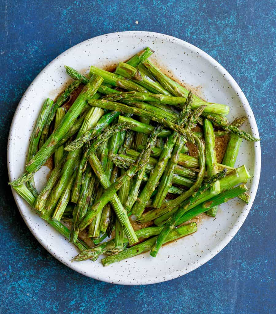 asparagus on a white plate with a blue background