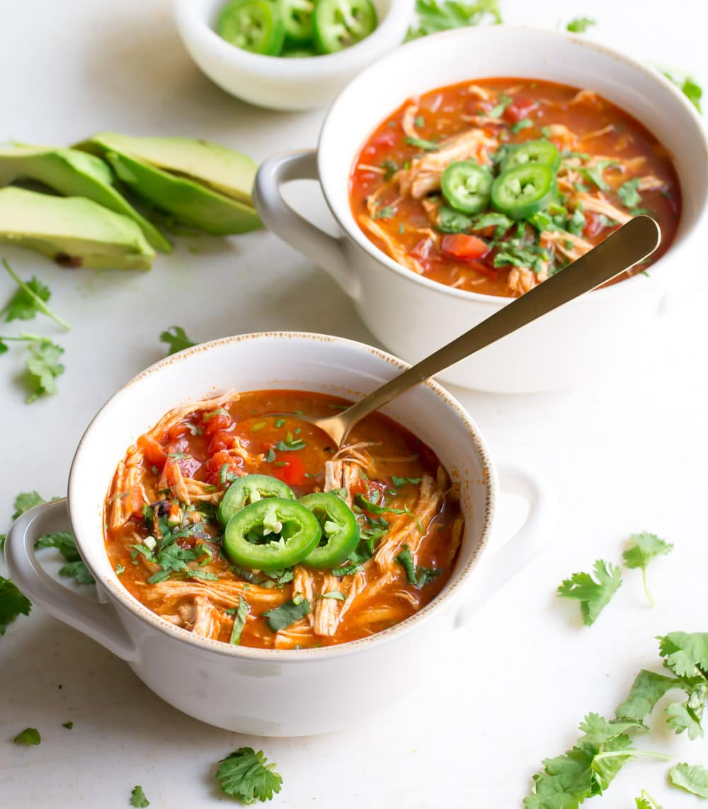 Two bowls of Chicken Tortilla-less Soup on a white background with a spoon in the bowl.