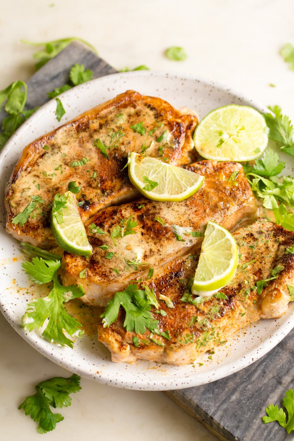 Spicy pork chops on a white plate with creamy sauce.