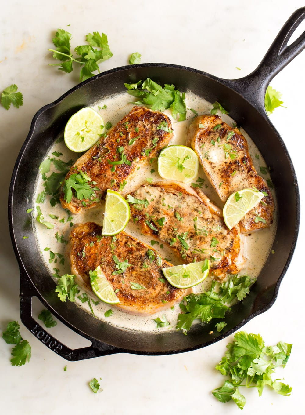 Pork chops in a creamy chipotle sauce in a cast iron skillet with lime wedges.