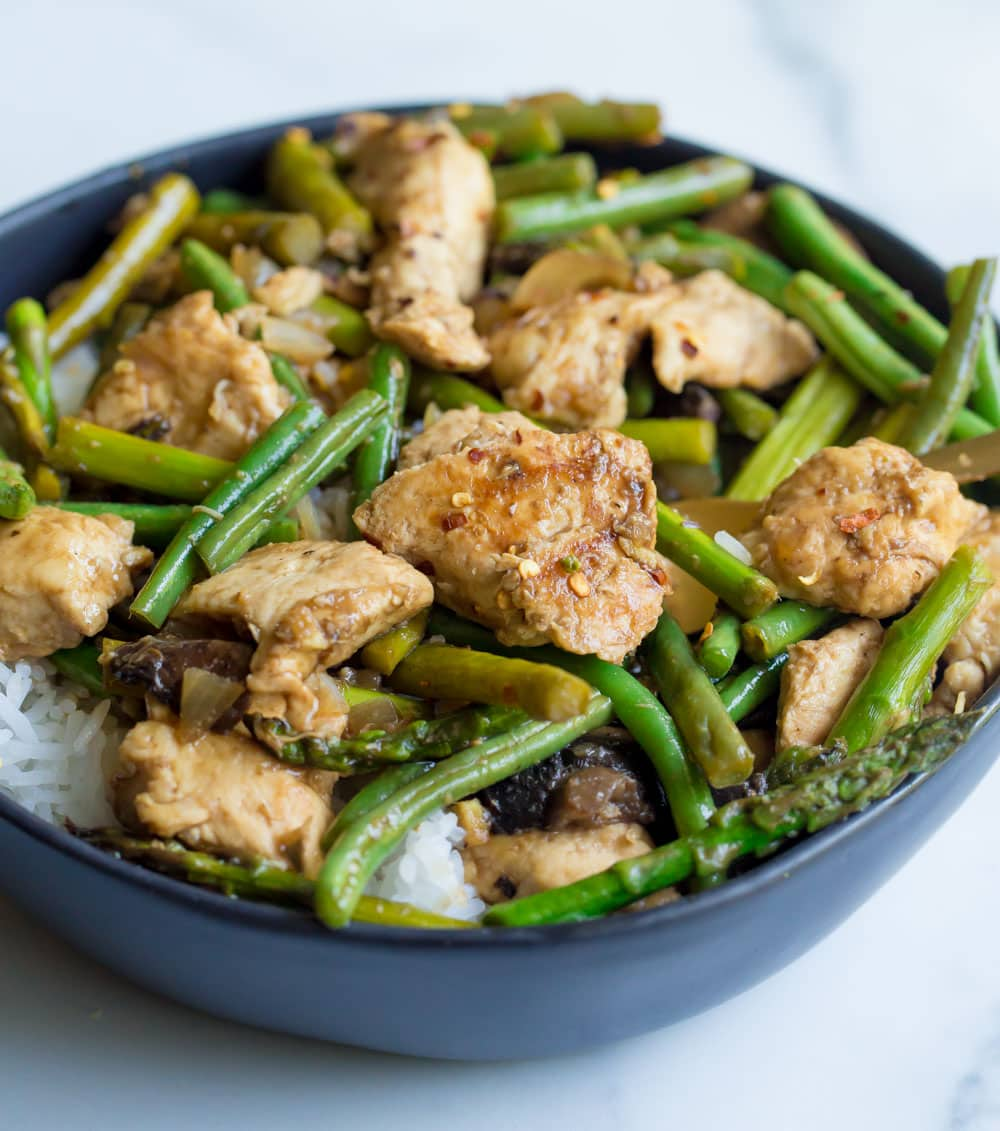 Balsamic honey chicken with asparagus in a black bowl.