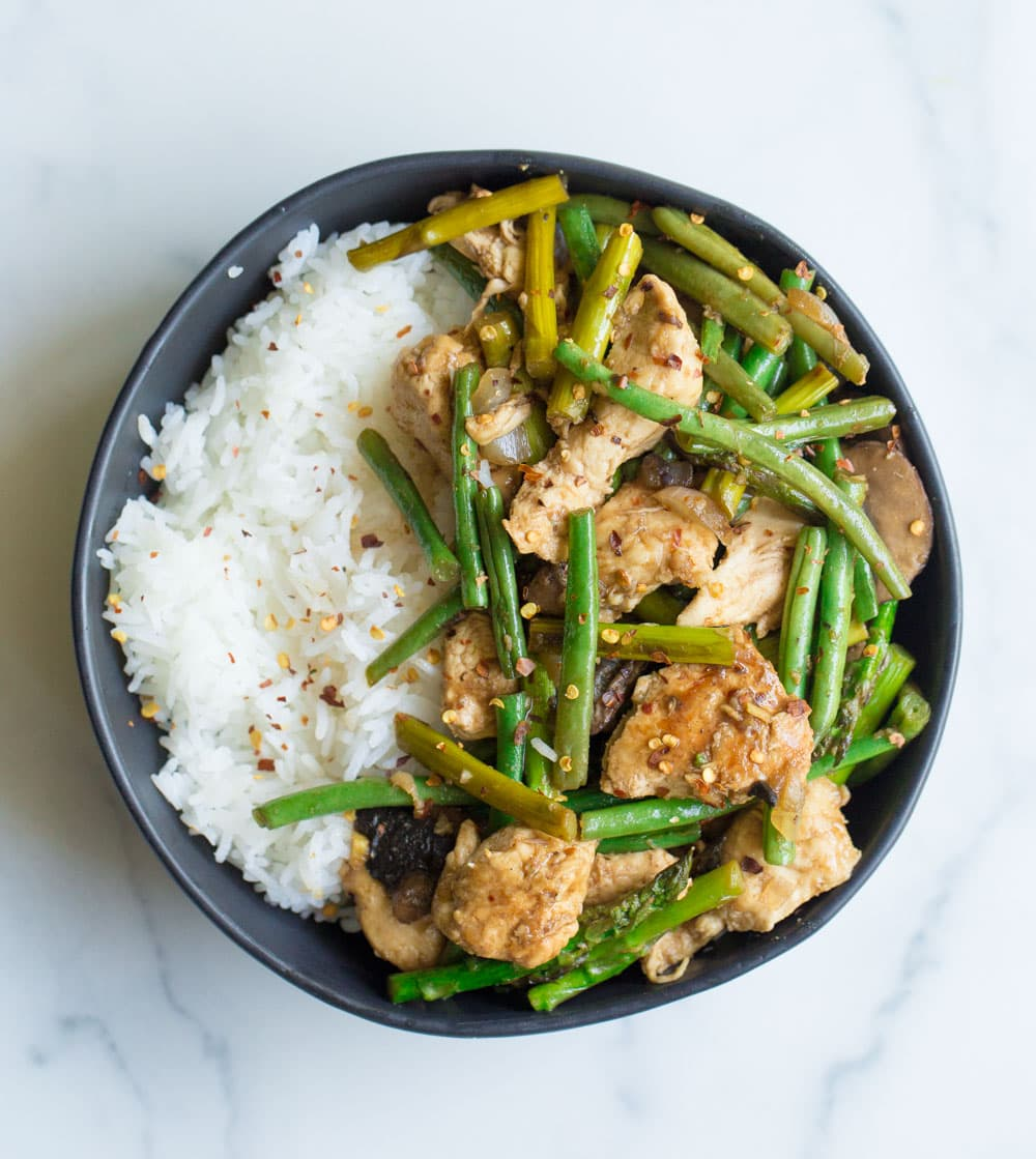 Balsamic honey chicken and asparagus in a black bowl with rice.