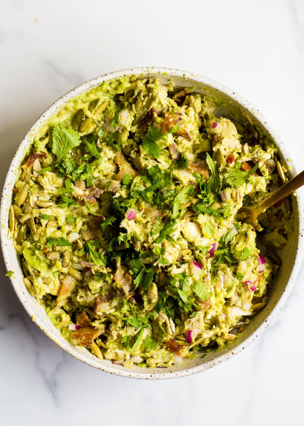 Avocado chicken salad in a white bowl on a white background