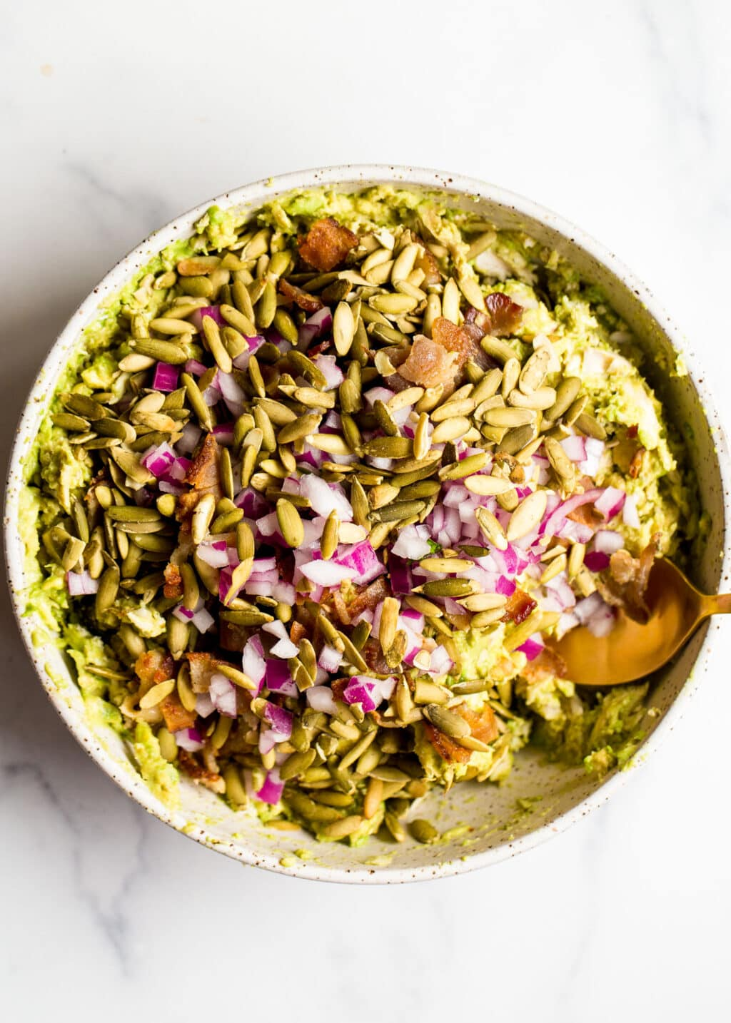 Avocado chicken salad with pumpkin seeds and red onion on top