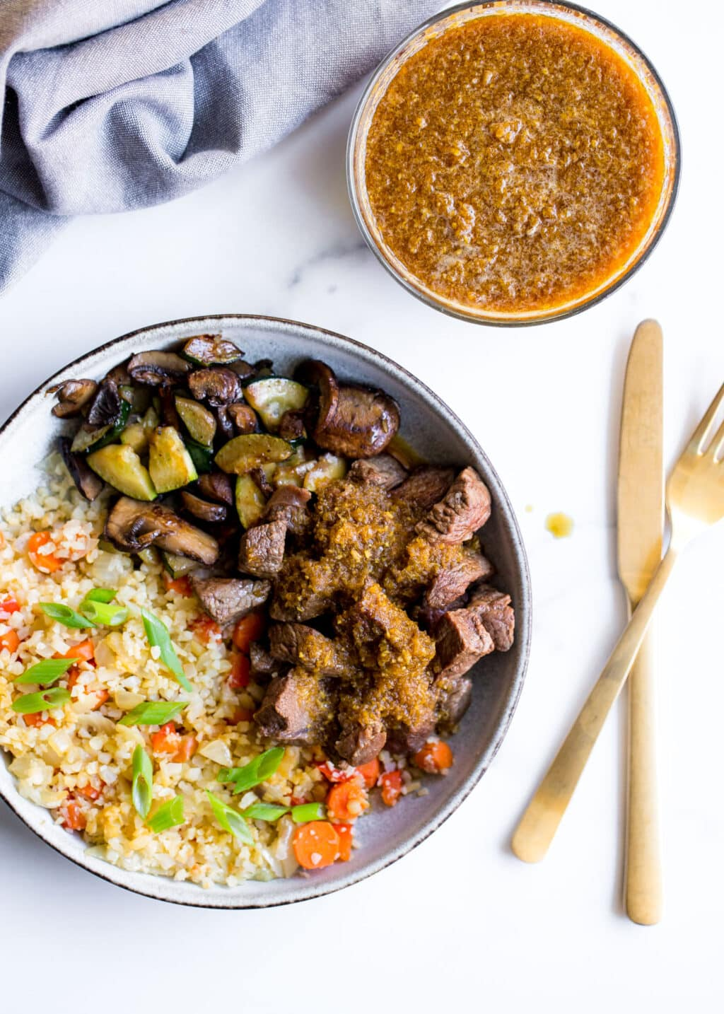 Bowl of steak and cauliflower rice on a white background with fork and knife.