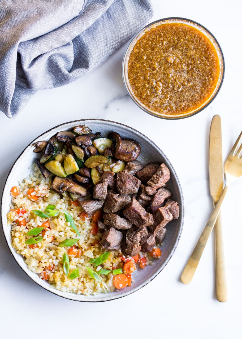 White background with bowl of steak and veggies in the middle. Gold fork and knife in the background.