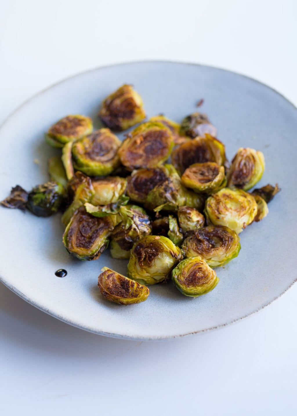 A white plate of brussels sprouts with balsamic drizzle on the side.
