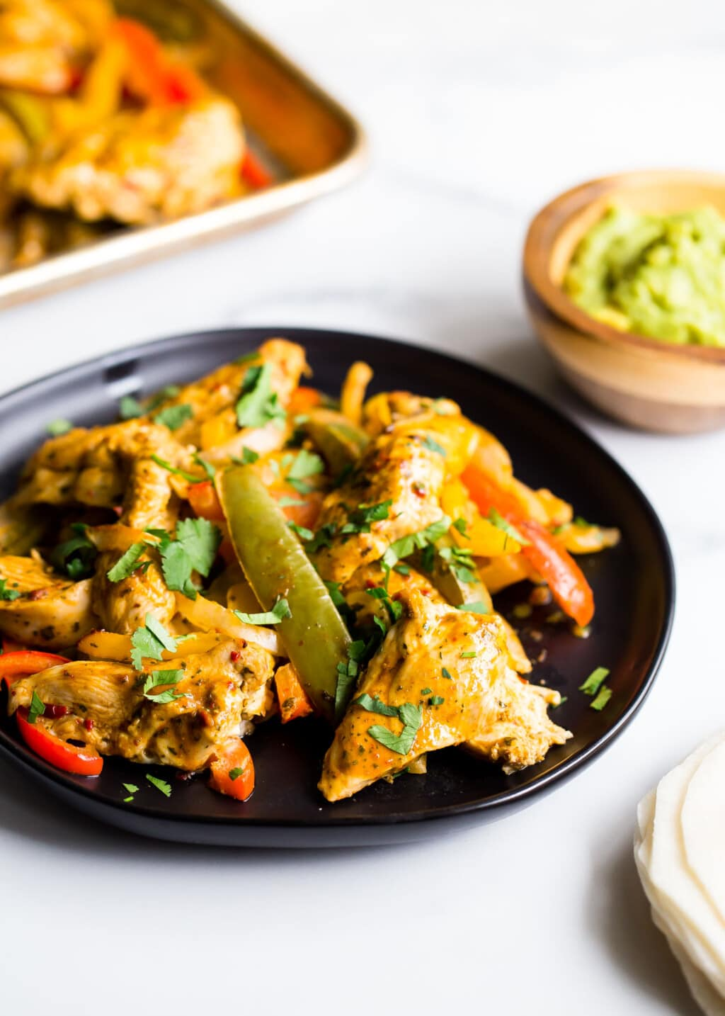 chicken and bell peppers on a black plate