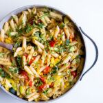 large saucepan filled with pasta and vegetables on a white background