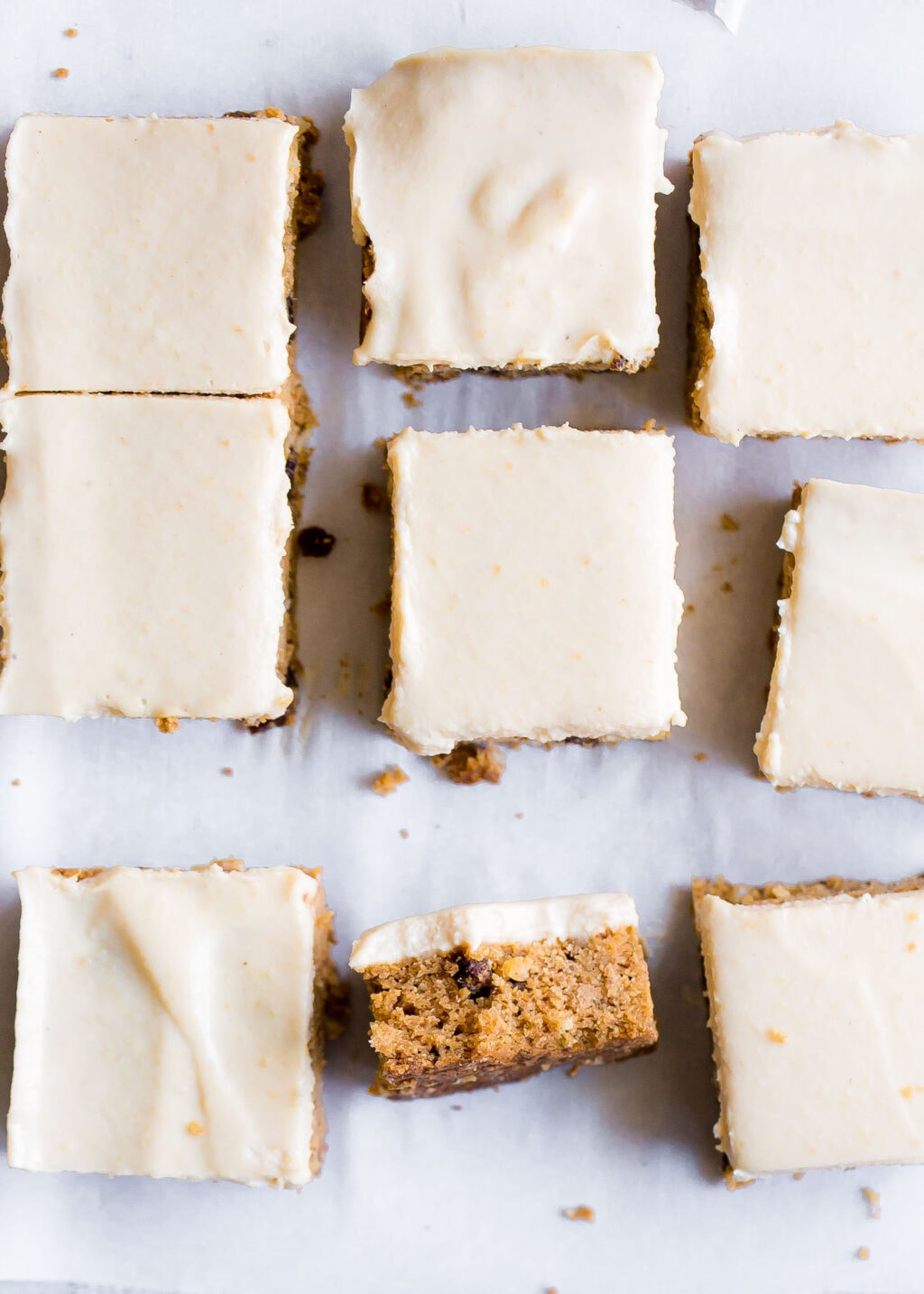 One carrot cake bar facing up, the rest are facing down on a white background.