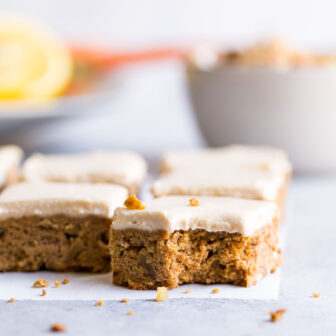 Carrot cake bar with a bite out of it on a gray background.