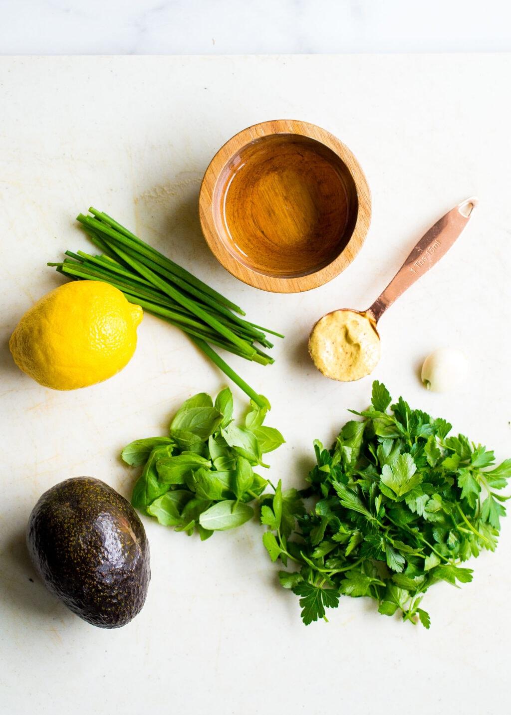 Fresh herbs, lemon, avocado, and dijon mustard on a white background.
