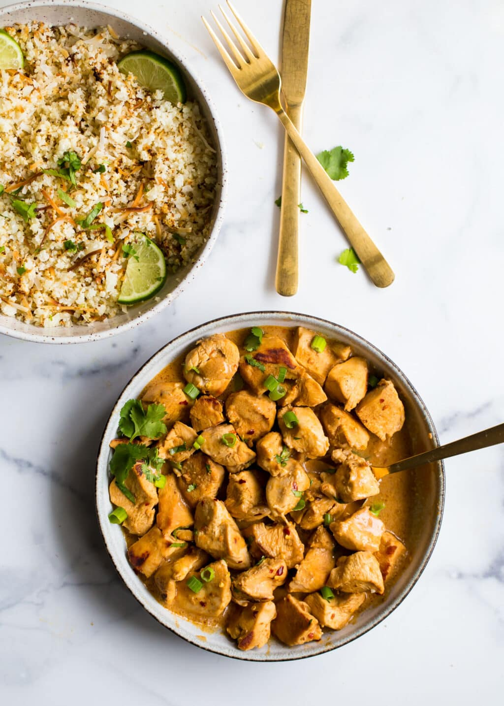 Cashew butter chicken in a white bowl with a bowl of cauliflower rice on top.