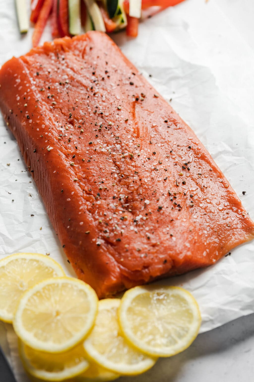 Raw salmon filet with salt and pepper, and lemon slices in the background.