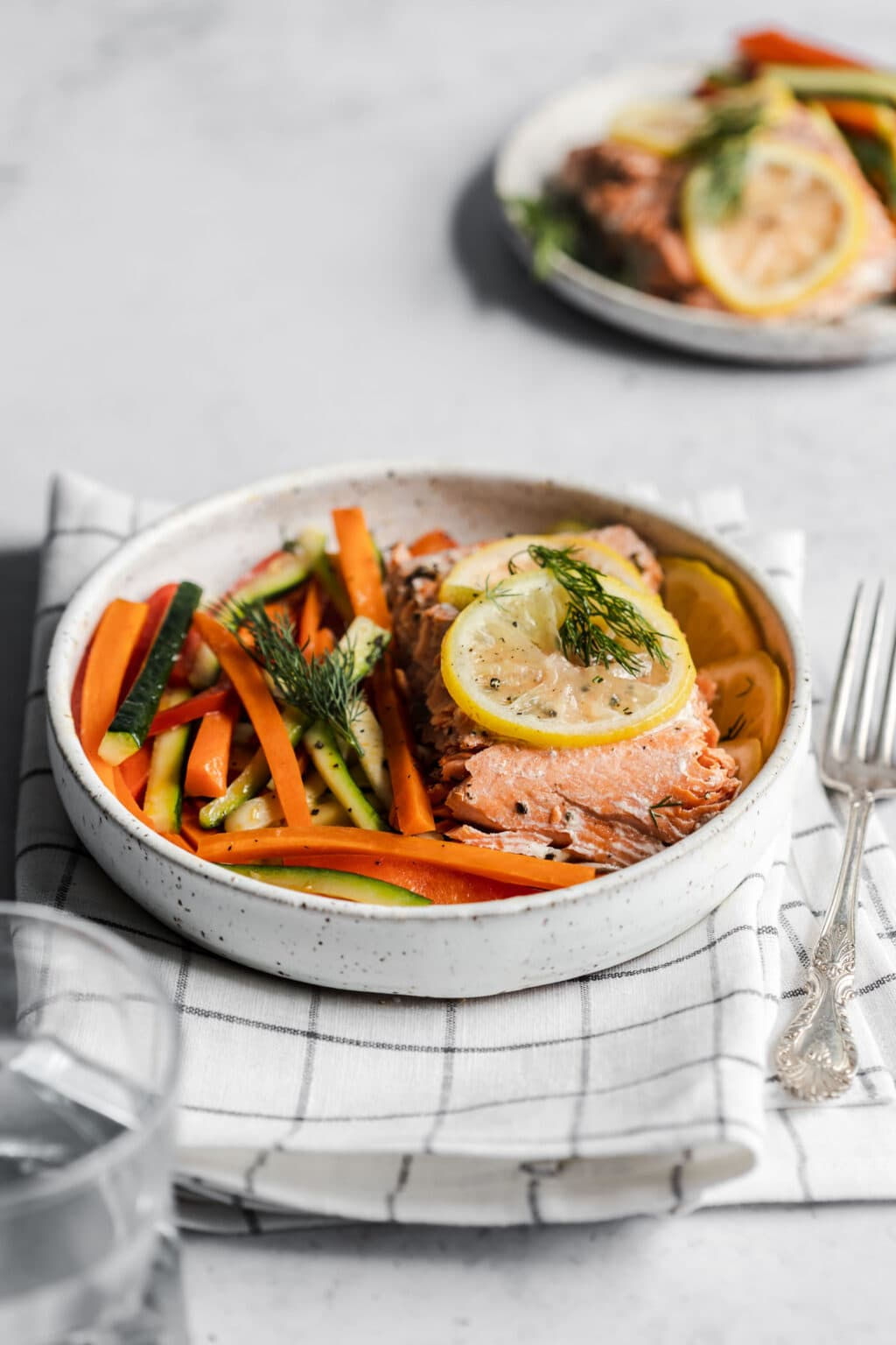 A plate of salmon and veggies on top of a dish towel and gray background.