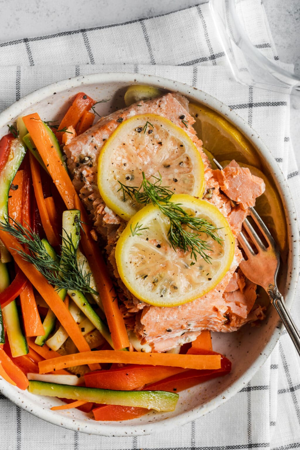 A white plate with salmon and vegetables on top of a dish towel.
