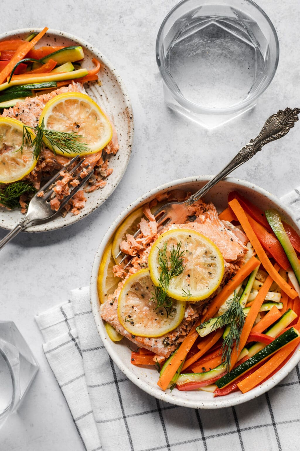 Two white plates of salmon with lemon slices and vegetables on a gray background.