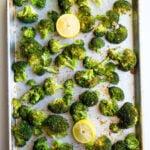 Roasted chopped broccoli on a sheet pan with lemons