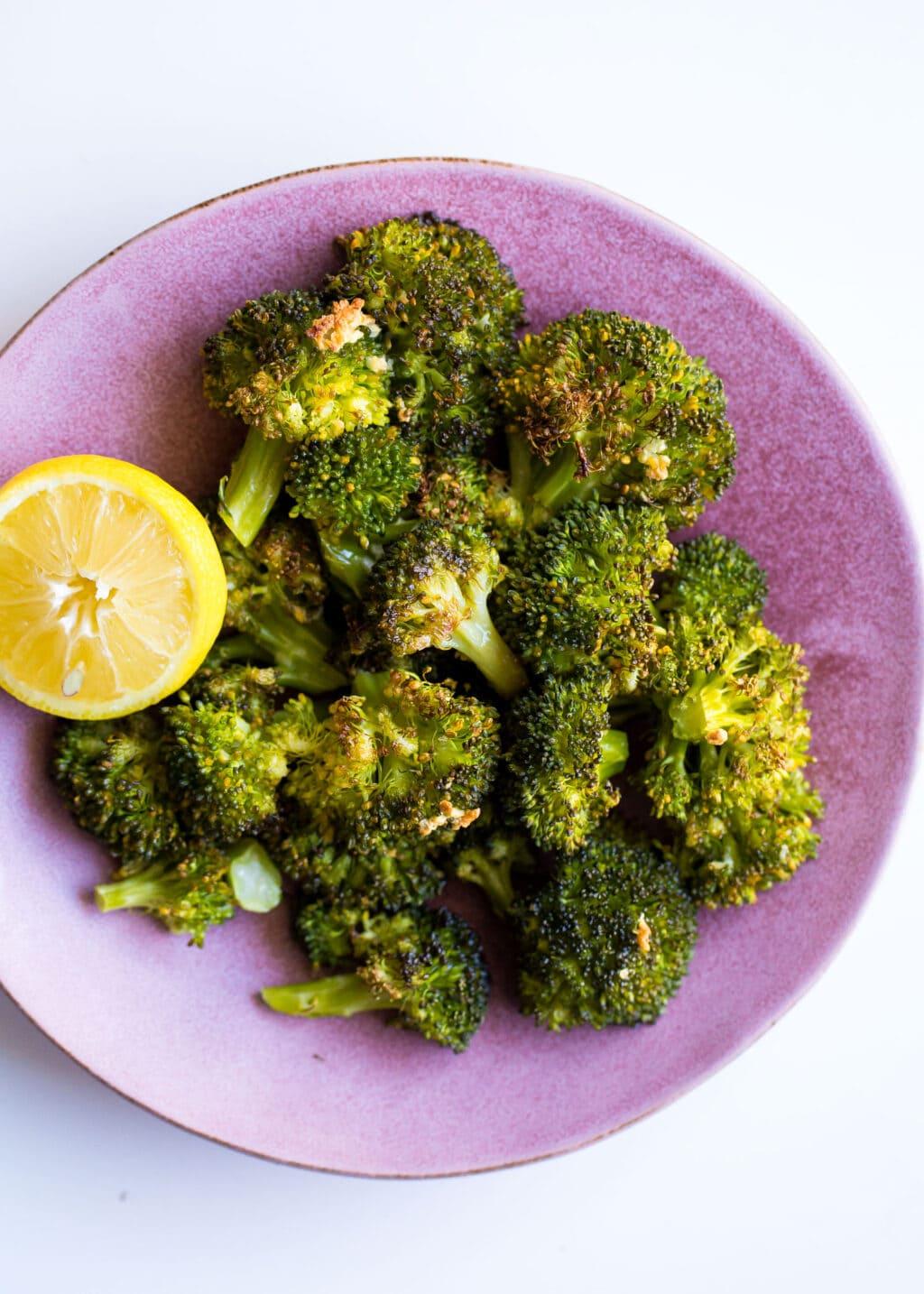 Roasted broccoli on a purple plate with a lemon slice.