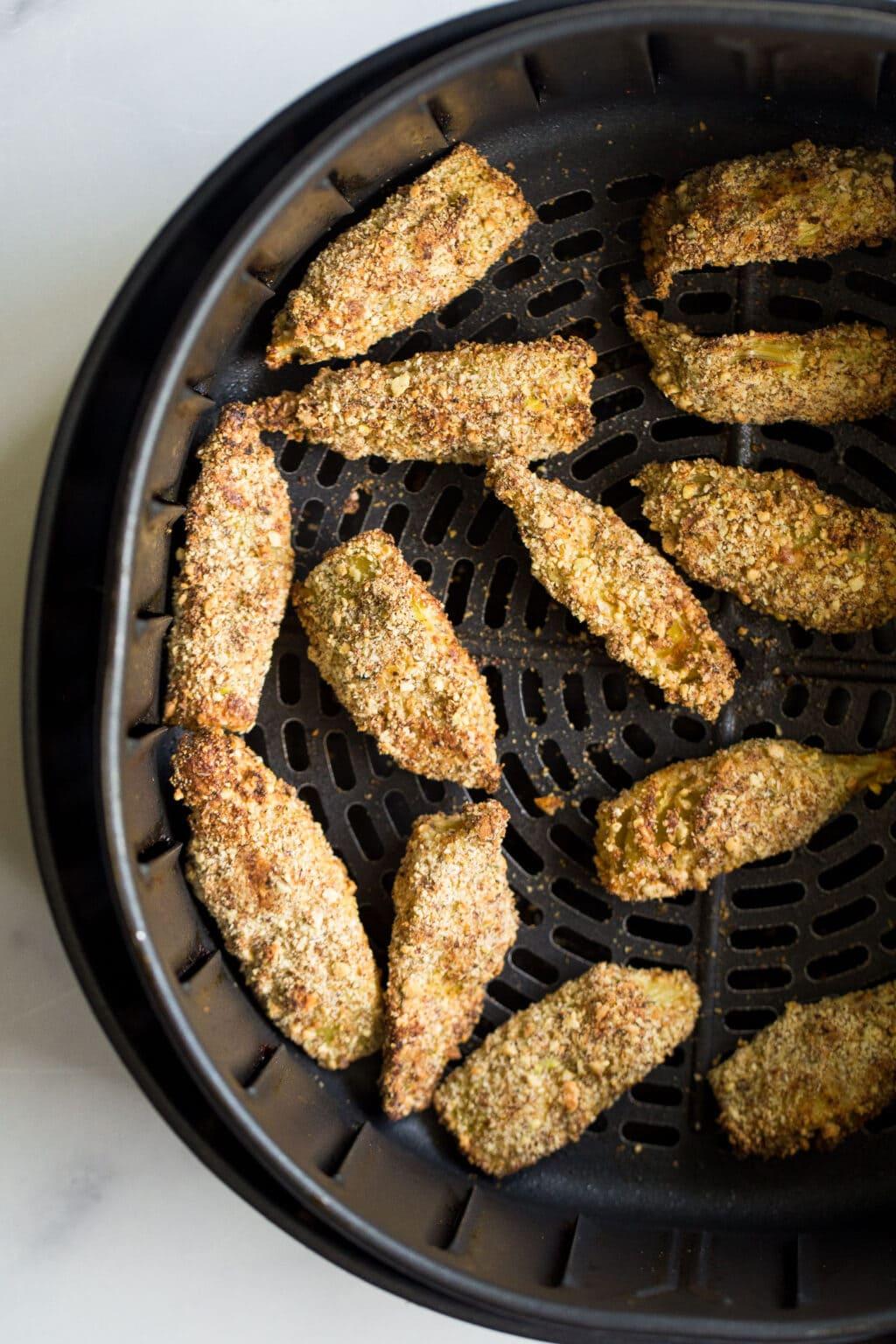 artichoke hearts in a crispy coating in the air fryer basket.