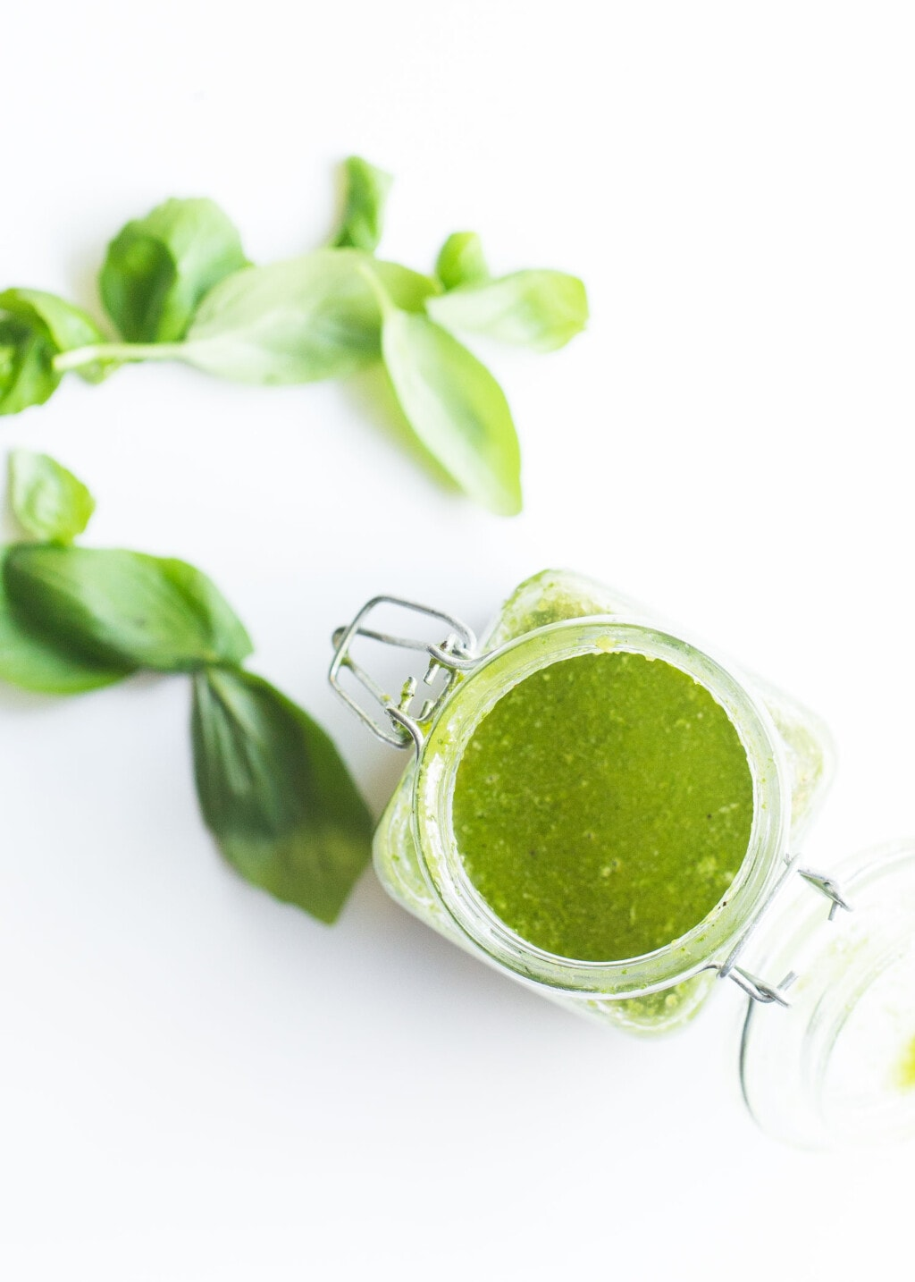 Jar of basil vinaigrette on a white background with basil leaves in the background