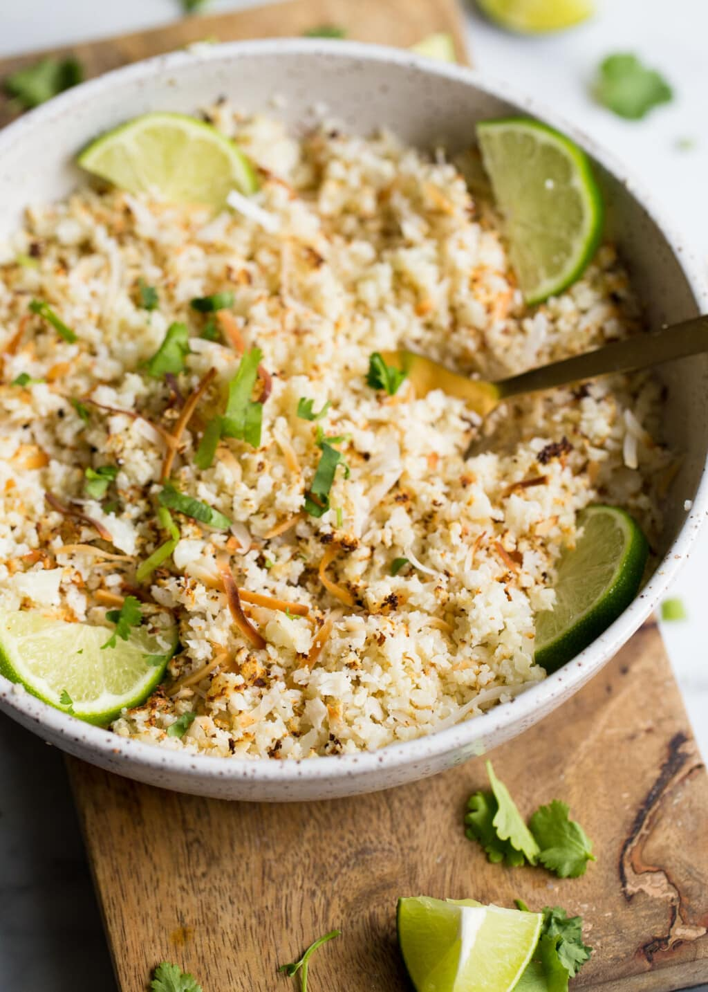 cauliflower rice in a bowl with lime wedges and coconut.