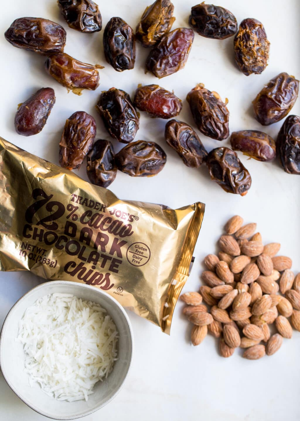 Dates, almonds, chocolate chips, and coconut flakes on a white background.