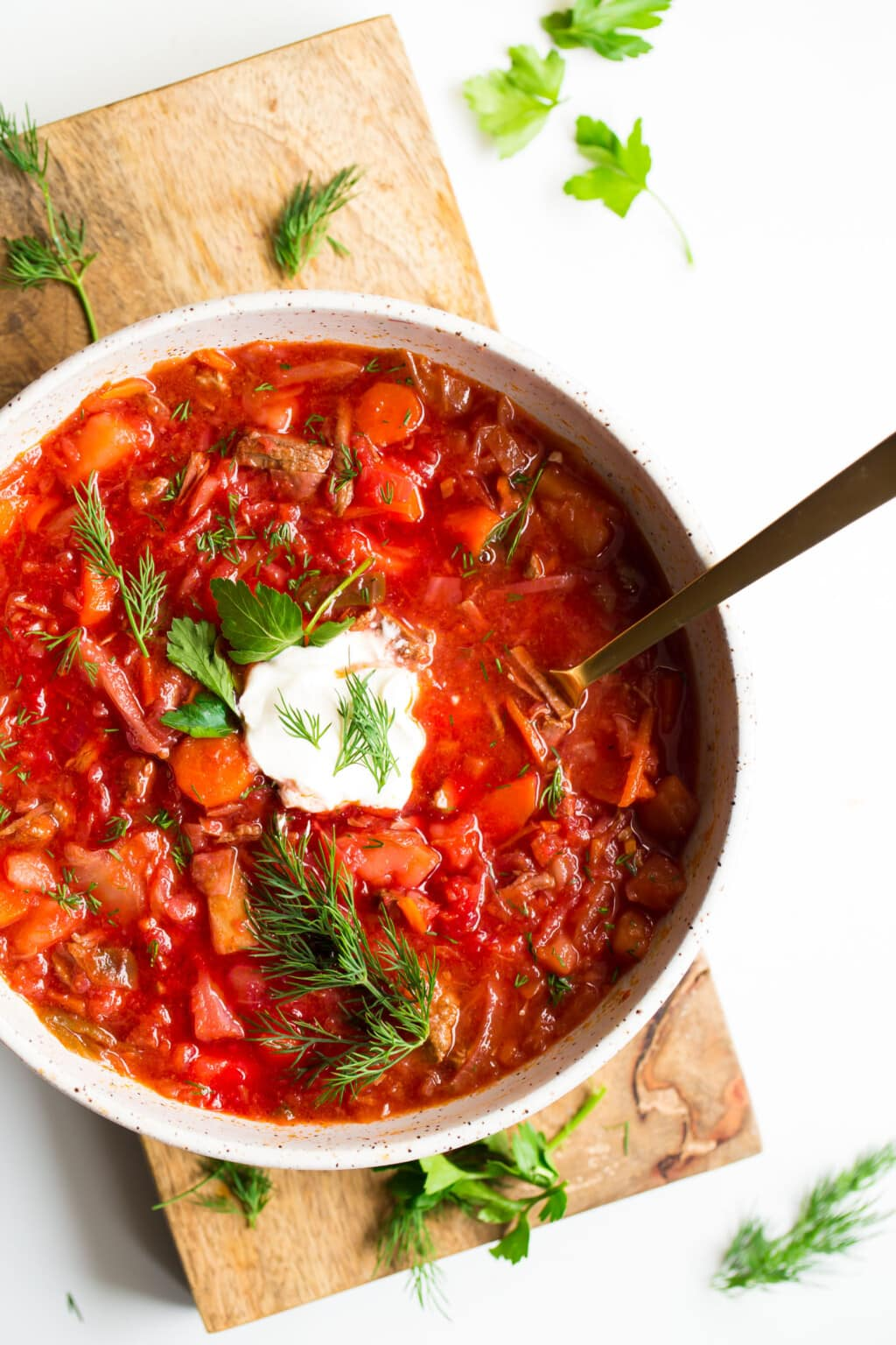 bowl of borscht soup in white bowl with sour cream on top