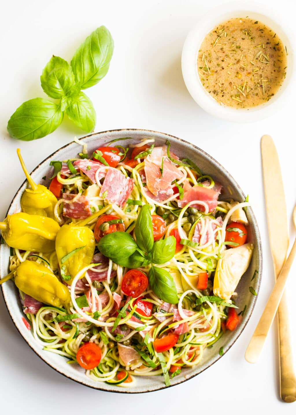 Bowl of zucchini noodles and veggies with salami and fresh basil on a white background.