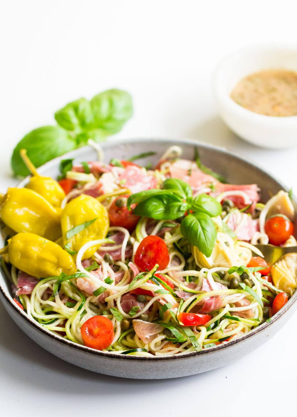Bowl of zucchini noodles salad with fresh basil and Italian dressing.