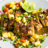 Sliced chicken with pineapple salsa on top.