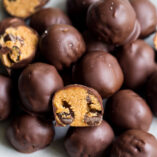 plate of chocolate chip cookie dough truffles with one truffle cut in half.