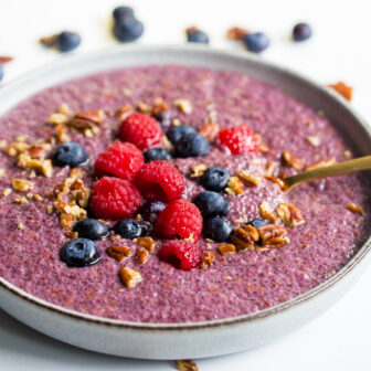 Bowl of chia porridge with berries on top on a white background with a gold spoon.
