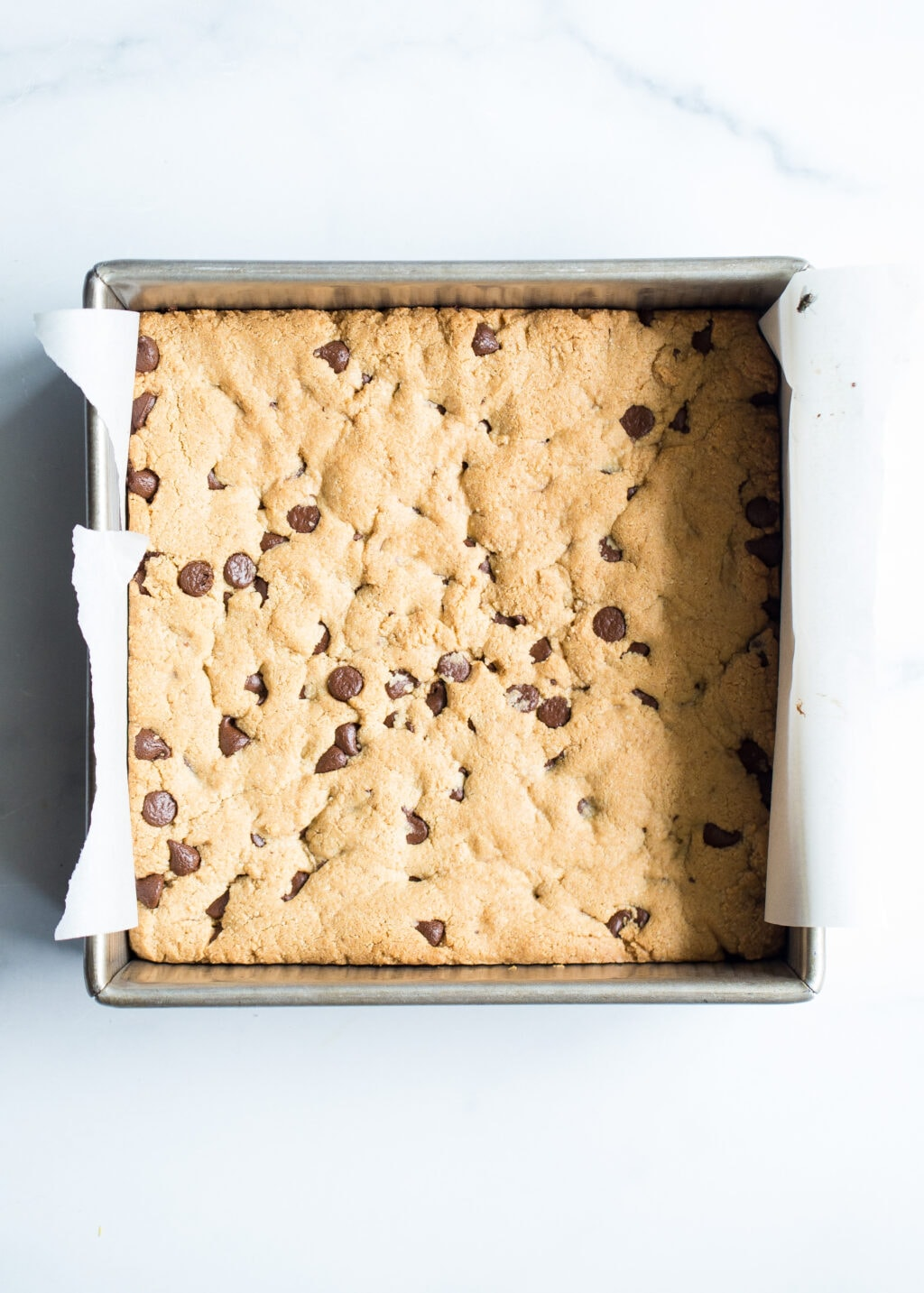 Chocolate chip cookie dough baked in an 8x8 inch pan with parchment paper.
