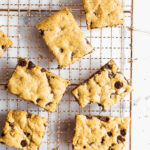 Chocolate chip cookie bars on a gold cooling rack.