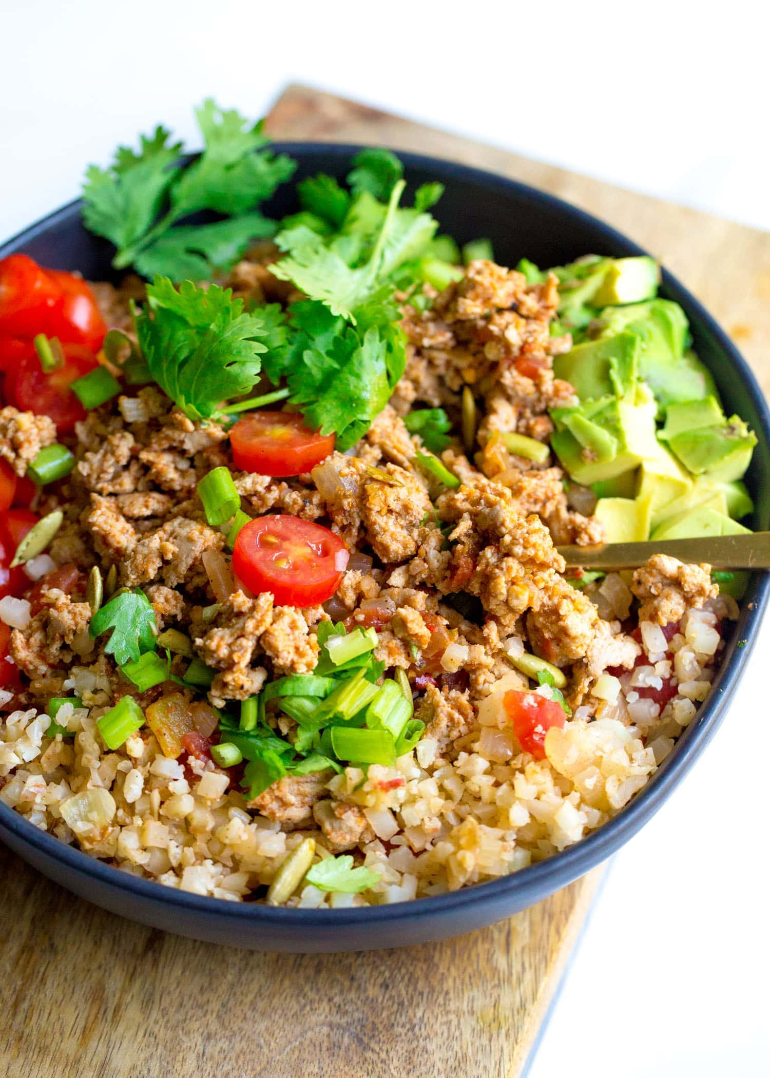Bowl of ground turkey taco meat on Spanish cauliflower rice with tomatoes and cilantro.