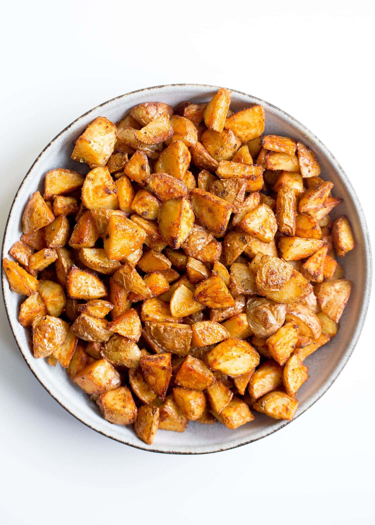 Bowl of crispy potatoes on a white background